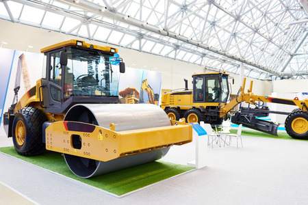 New road roller and motor grader on exhibition Фото со стока
