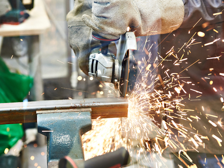 Metal cutting with angle grinder with sparks Фото со стока