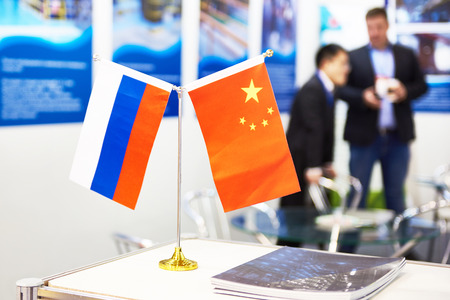 Flags of China and Russia at a business exhibition Фото со стока