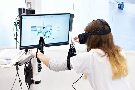 Woman on stand with a virtual reality device for the rehabilitation of people