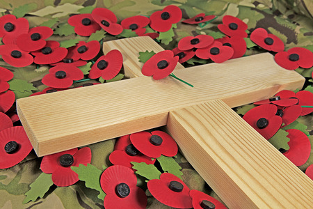 A wooden cross laying on a green camouflaged cloth surrounded by traditional imitation poppies