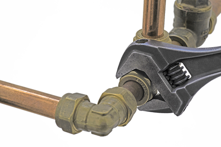 An adjustable wrench tightening up a compression tee fitting to 15mm copper pipework  on a white  background
