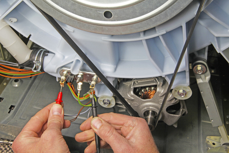 Domestic electrical appliance technician holding multimeter probes onto a heating element to test for continuity
