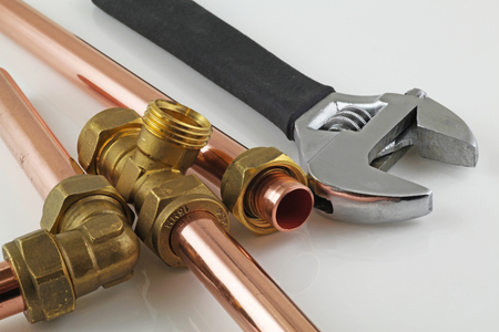Adjustable wrench, 15mm copper piping and brass joints laid together against a grey background Banque d'images