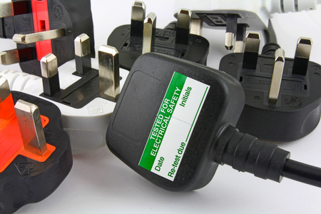 side view of plugs –  Background of  three pin plugs with top of plug  with test sticker Banco de Imagens