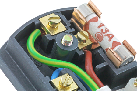 Three pin plug – An isolated UK plug on a white background with its cover removed showing the fuse and wiring