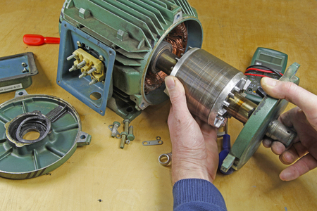 3 상 유도 전동기 베어링 수리 - 샤프트 베어링 교환 전 고정자에서 회 전자를 제거하는 수리공 스톡 콘텐츠