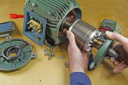 Reparatur von Drehstrom-Induktionsmotorlagern Ein Monteur / Techniker, der den Rotor vom Stator entfernt, bevor die Wellenlager ausgetauscht werden