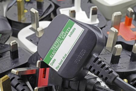 プラグ-観テスト ステッカー付きプラグの上部に 3 つの pin プラグのぼやけた背景を計画します。