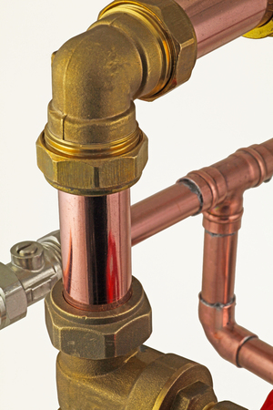 pipework close up -  isolated  copper pipe with compression fittings on top of blurred pipework on an white background