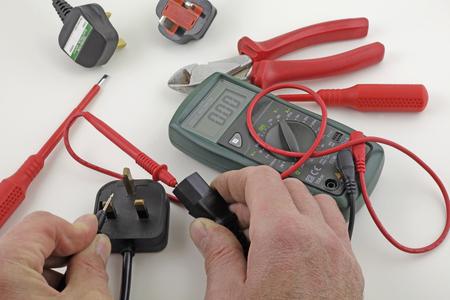 Test de continuité de la terre - Un électricien teste la terre d'un câble d'alimentation avec un multimètre Banque d'images - 83932509