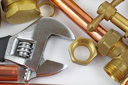 New copper pipework ready for construction – Adjustable wrench, 15mm copper piping and brass joints laid together against a grey background Stockfoto