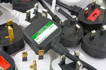 bovenaanzicht van pluggen - Onscherpe achtergrond van driepolige stekkers met top van stekker met teststicker Stockfoto