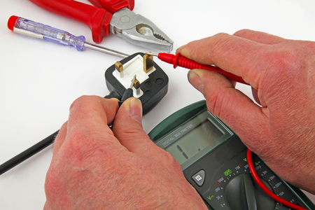 Earth insulation testing – An electrician testing for a earth fault  betweenthe live cable and earth with a multimeter Stock Photo