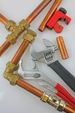 New copper pipework ready for construction – Adjustable wrench, 15mm copper piping and brass joints laid together against a grey background