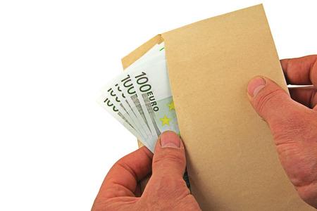 Soldi - Un paio di mani che tengono e spargono cento banconote in euro in una busta marrone Archivio Fotografico - 92357153
