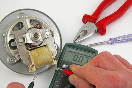 wall socket: Appliance testing – An engineer fault finding an electric fan motor .