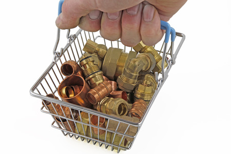 Plumbing – A hand holding a shopping basket containing copper and brass fittings on an isolated white background,