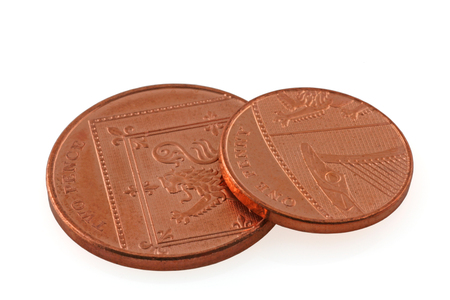 Money – An one pence coin resting on a two pence coin on an isolated white background