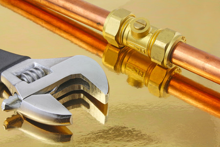 Plumber  pipework – An adjustable wrench and  15mm copper pipework ith a compression ball valve laying on a reflective gold background