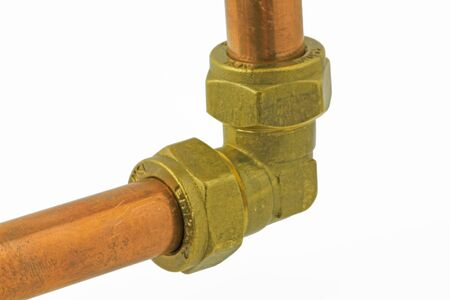 Plumbing pipework  –  A compression fitting elbow with pipework isolated on a white background
