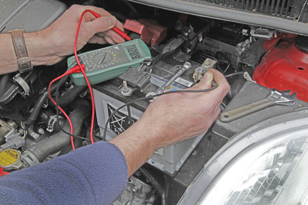 Car battery – A man holding the probes of a multimeter onto the battery terminals to check voltage of car battery
