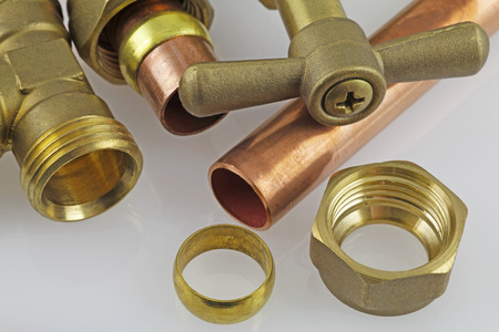 Plumbing – A close up view  of a compression fitting on a grey background.