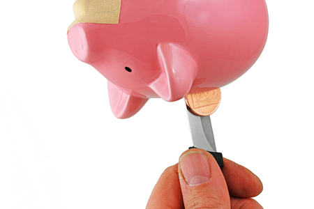 Piggy bank – A pink  ceramic piggy bank being held upside down with a plaster on it mouth, and a knife being used to remove any money Stok Fotoğraf