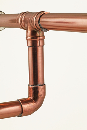 Pipework and fittings -  Copper pipe and solder fittings isolated on a white background