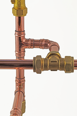 Pipework and fittings -  Copper pipe with compression and solder fittings isolated on a white background