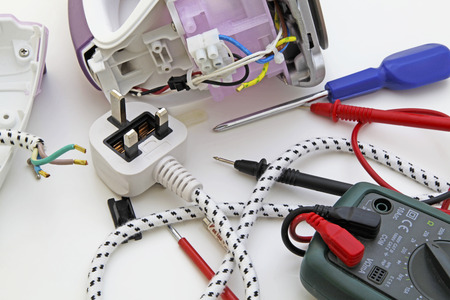 Appliance testing – An appliance engineer repairing an electric iron.
