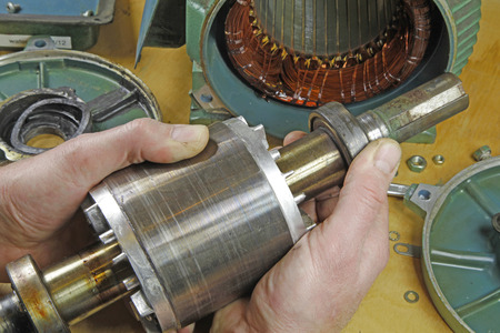 Three phase induction   motor bearing repair – A fittertechnician  checking motor windings resistance readings with a multimeter and  checking for faults on shaft bearings Stock fotó