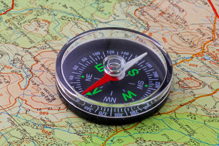 Compass and map – A magnetic compass being used to orientate a map to the ground Фото со стока