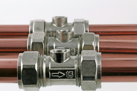 plumbing ball valve – Three ball valves connected to copper pipework isolated on a white background Stock Photo
