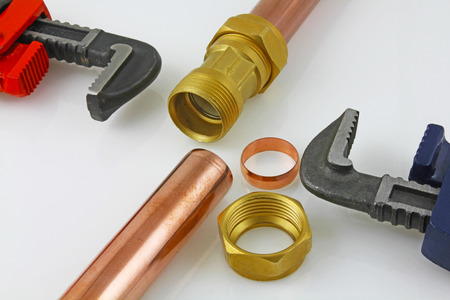New copper pipework ready for construction – Adjustable wrenches, 15mm copper piping and brass joints laid together against a grey background