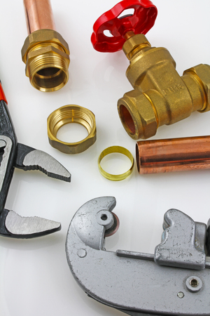 New copper pipework ready for construction – Adjustable wrench, pipe cutter,  15mm copper piping and brass joints laid together against a grey background