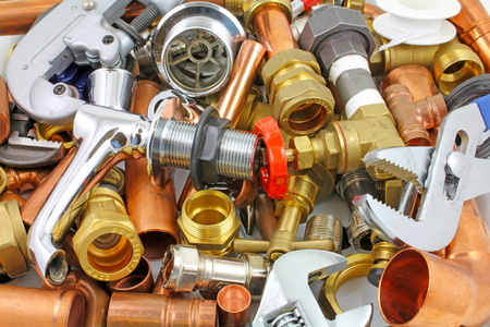Plumber's pipes and fittings   –    Random mixture of copper pipe and brass fittings ideal for use as a website header  background Banque d'images
