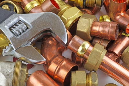 Plumber's pipes and fittings   –    Random mixture of copper pipe and brass fittings ideal for use as a website header  background