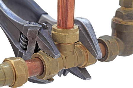 Plumber tightening up pipework – Two adjustable wrenches tightening up tee-fitting on 15mm copper pipework isolated on a white background Banque d'images