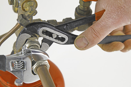 Plumber tightening up pipework – Two adjustable wrenches tightening up tee-fitting on 15mm copper pipework isolated on a white background