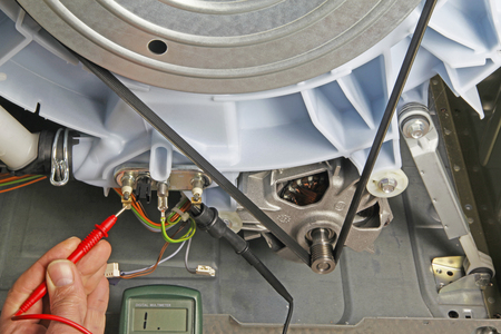 Washing machine appliance repair – Domestic electrical appliance technician holding multimeter probes onto a heating element to test for continuity