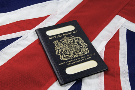 Flag and passports–  An old style united Kingdom passport on a Union Jack background
