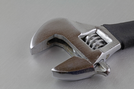 Wrench – An adjustable wrench laying on a metal plate Imagens