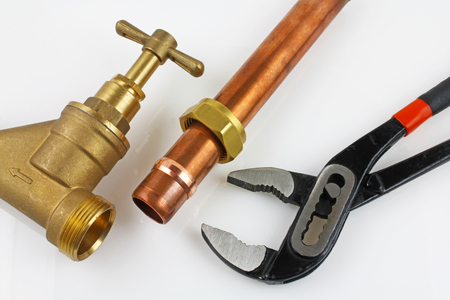 New copper pipework ready for construction – Adjustable wrench, 15mm copper piping and brass joints laid together against a grey background Stock fotó