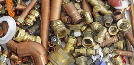 Plumbers pipes and fittings   –    Random mixture of copper pipe and brass fittings ideal for use as a website header  background