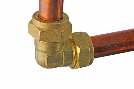 Copper pipework –  Two sections of copper pipes connected  to a compression elbow isolated on a white background,