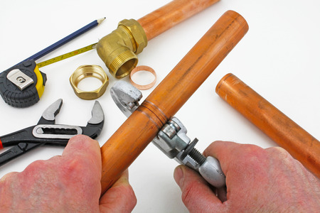 Copper pipe cutting – A pair of hands using a pipe cutter on copper with plumber bits and pieces in the background