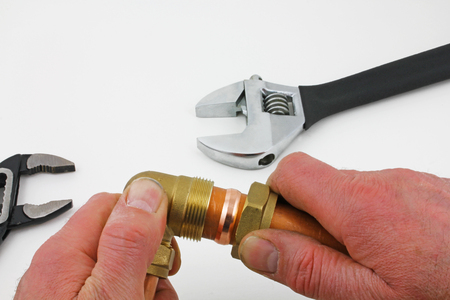 Compression elbow make up – A pair of hands assembling a compression elbow with two wrenches laying on a grey background