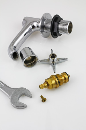 Sink tap repair – A stripped down sink tap and spanner laying on a grey background