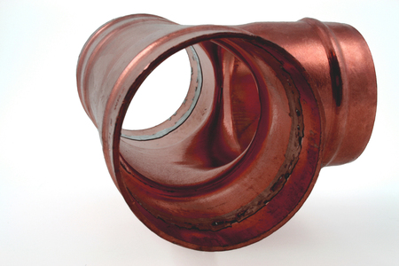 Plumbers fitting – A close up view of a solder ring tee fitting resting on a grey background